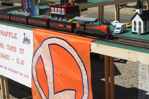 The Lionel Club Ambassador TMB Model Train Club modular layout runs the Long Island passenger train set down the track at the Bellmore Street fair on the