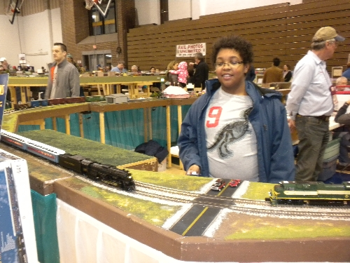 CASG Lionel Club Ambassador catches the eye of a boy noticing The Polar Express Train at High Wheeler 16 at Harper College in Palatine IL