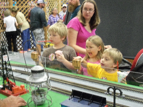 Families gathered to view the trains running on the Wichita Toy Train Club Lionel Club Ambassador layout at the 2016 Kansas State Fair
